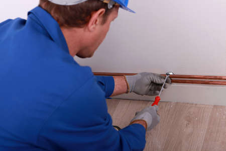 securing: Plumber securing pipe to wall Stock Photo