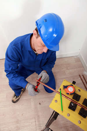 Plumber cutting copper pipe Stock Photo - 13795785