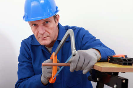 sawing: Artisan sawing copper pipe
