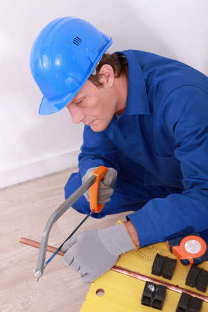 Man sawing copper pipe Stock Photo - 13843308