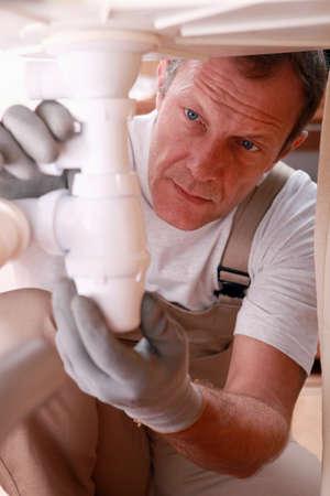 tradesperson: Plumber fixing a siphon Stock Photo