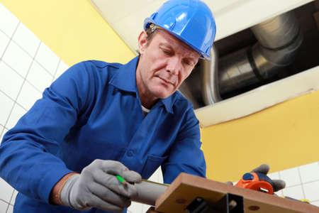 sewer: Plumber cutting grey pipe
