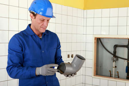Plumber working on public restroom photo