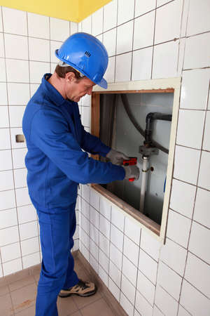 journeyman: Plumber working in a tiled room