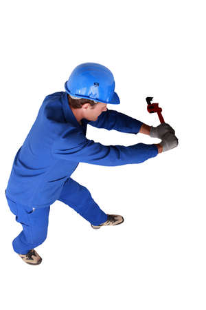 Top view of a plumber wrestling with a large wrench and pipework