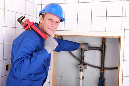 experienced: Experienced plumber using a large wrench in a bathroom Stock Photo