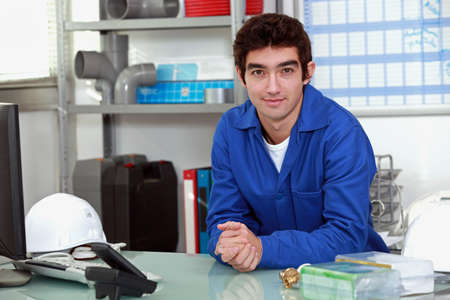 jumpsuite: young man wearing a blue jumpsuite at office
