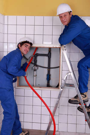 Plumbers working in a tiled room photo