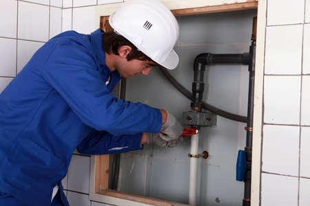 screwing: Plumber screwing pipe