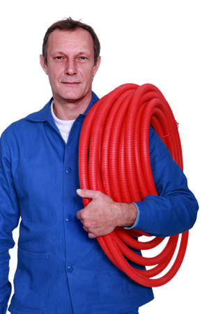 fully-fledged plumber carrying red hose photo