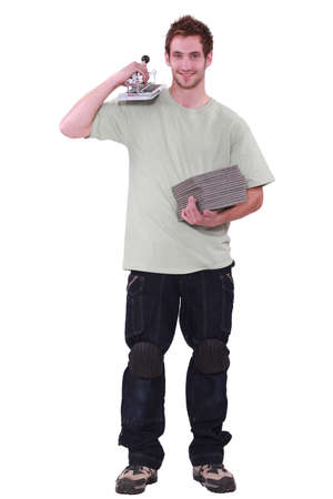 a young man holding tiles and a tiles cutter Stock Photo - 13802005