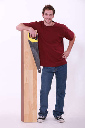 Man stood with laminate flooring and saw photo
