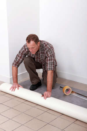 Man unrolling carpet roll photo