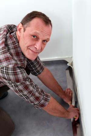 rigging: Man adjusting carpet Stock Photo