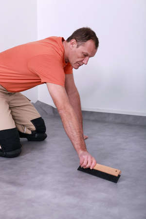 adherent: man laying linoleum Stock Photo