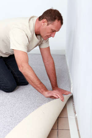 kneel: handyman is laying fitted carpet