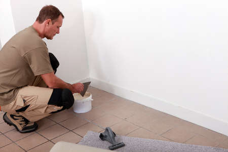 fitted: handyman laying fitted carpet