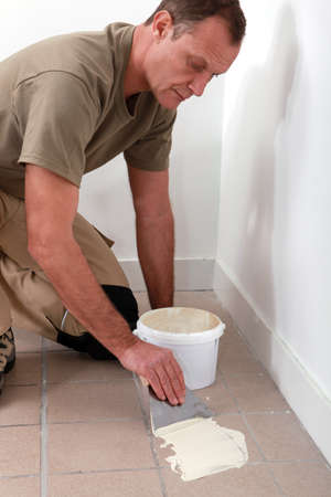 tile adhesive: Man spreading tile adhesive on old tiles
