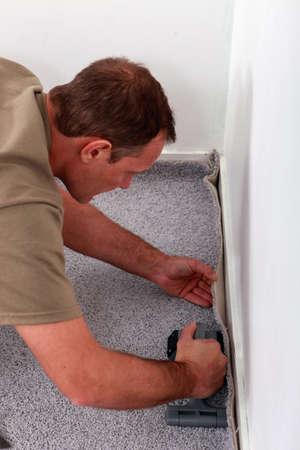 carpet and flooring: Man laying carpet