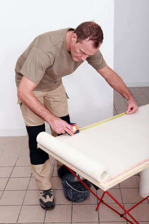 Decorator measuring a roll of wallpaper photo