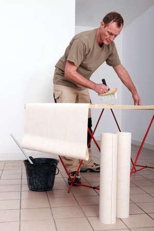 pegamento: Hombre poner pegamento en el papel pintado Foto de archivo