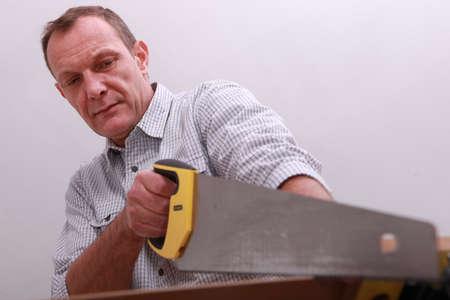 serrucho: De mediana edad carpintero con sierra de mano Foto de archivo