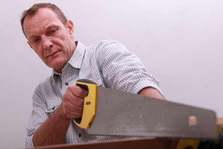 Middle-aged carpenter using hand-saw photo