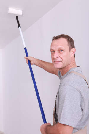 Decorator using a long roller to paint a ceiling photo