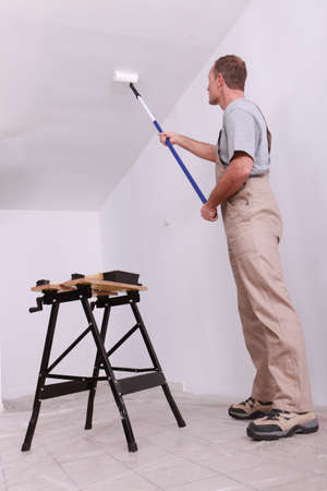 wall angle corner: Man painting ceiling Stock Photo