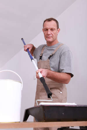 Decorator dipping his ceiling roller into a tray of white paint photo