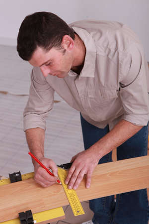 Man measuring wooden plank photo