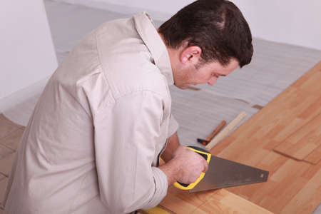 Laborer sawing laminate floor photo