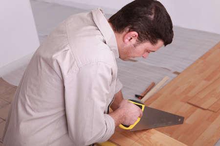 reforming: Laborer sawing laminate floor