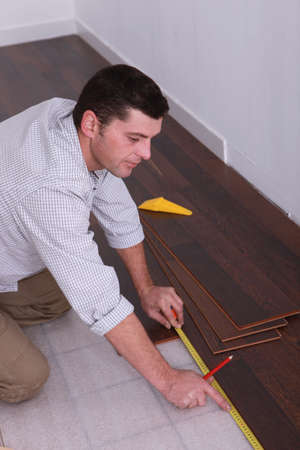 tongue and groove: Man fitting a wooden floor