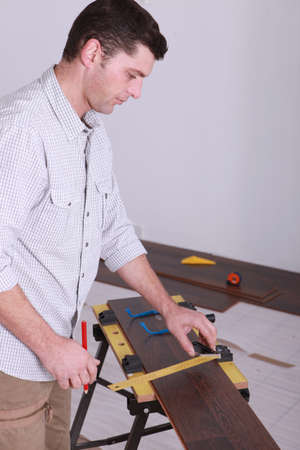 Man measuring plank of wood photo