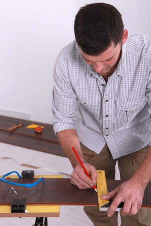 Closeup of a man marking a straight line on a piece of wooden flooring photo