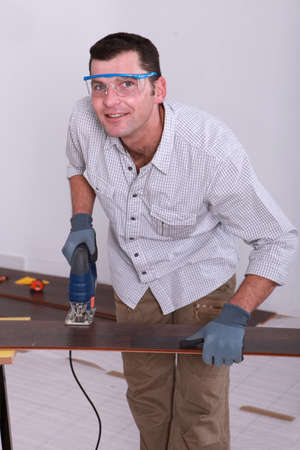 tongue and groove: Handyman wearing safety goggles and cutting a piece of wooden flooring with a jigsaw