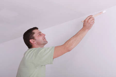 wall angle corner: Painter painting a ceiling corner