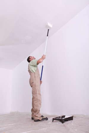 man painting: Mansard roof man painting Stock Photo
