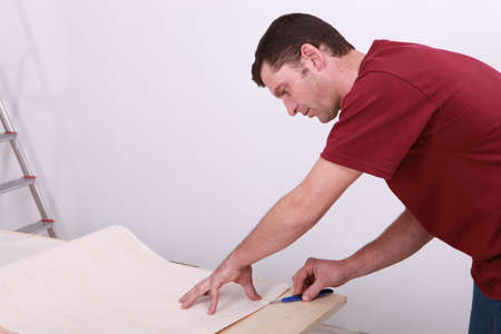 bent over: Tradesman cutting a sheet of paper