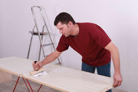 gluing: Man gluing wallpaper