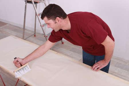 broad: Man gluing paper
