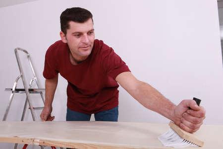 gluing: Man gluing paper
