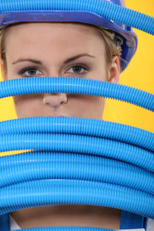Female construction worker peeking through corrugated tubes Stock Photo - 13811306