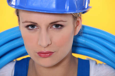 female plumber holding pipes photo