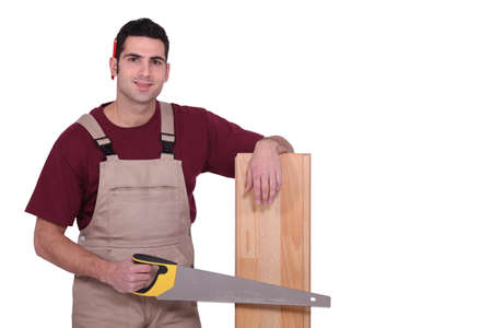 Carpenter with floorboards and a handsaw photo