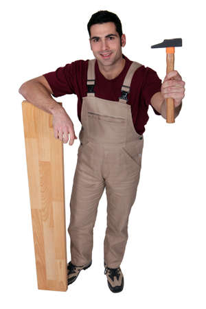 Man with a hammer and wooden floorboard photo