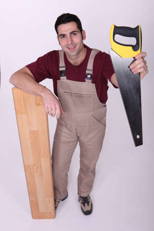 supported: Craftsman with saw and wooden slat Stock Photo