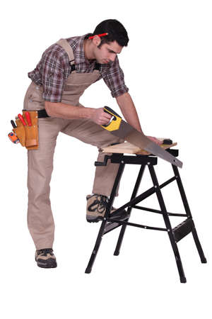 Handyman sawing a plank of wood photo