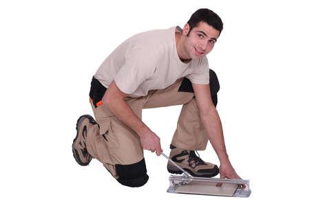 Man kneeling to cut tile to size photo